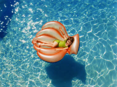 Girl floating on orange seashell