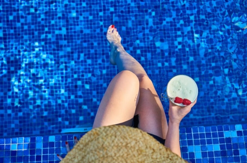 Woman sitting on pool edge after tile cleaning